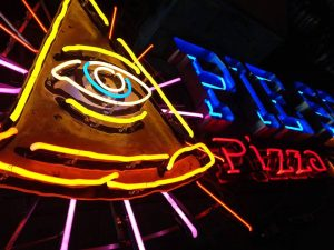 neon sign for pie society pizza with illuminati eye on a piece of pizza