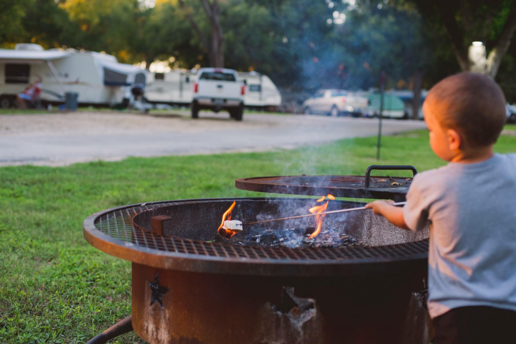 little boy making smores around campfire